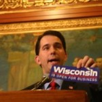 "Scott Walker holds up a ""Wisconsin is Open for Business"" bumper sticker"