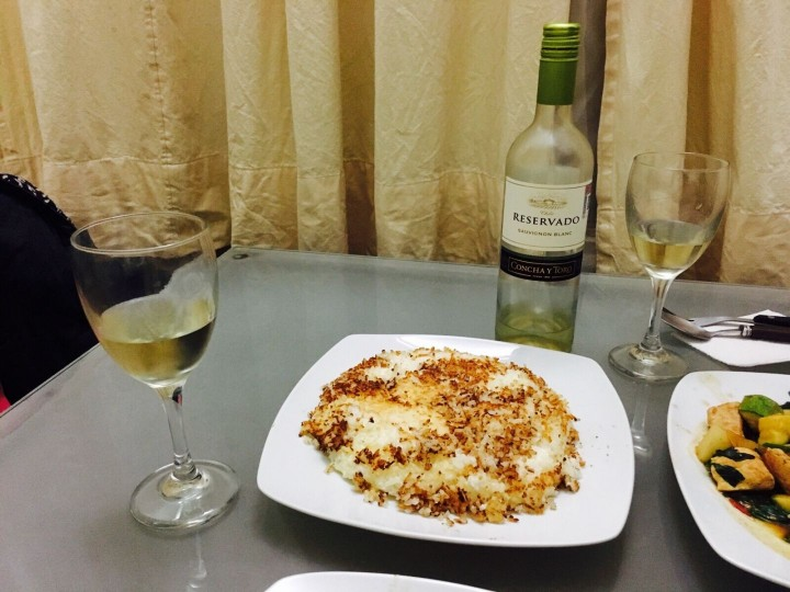 persian rice dish on table with wine