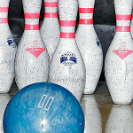 A bowling ball about to strike bowling pins