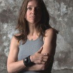 Photo of Ani DiFranco wit arms crossed, looking at the camera.