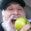 Close up of comedian Frandu as he bites into an apple