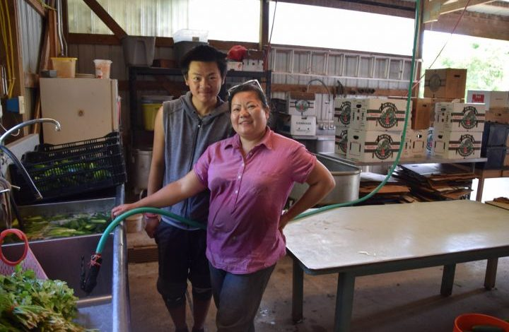 Yee Ythao and her son Pong Yang standing at the sink in the pack shed