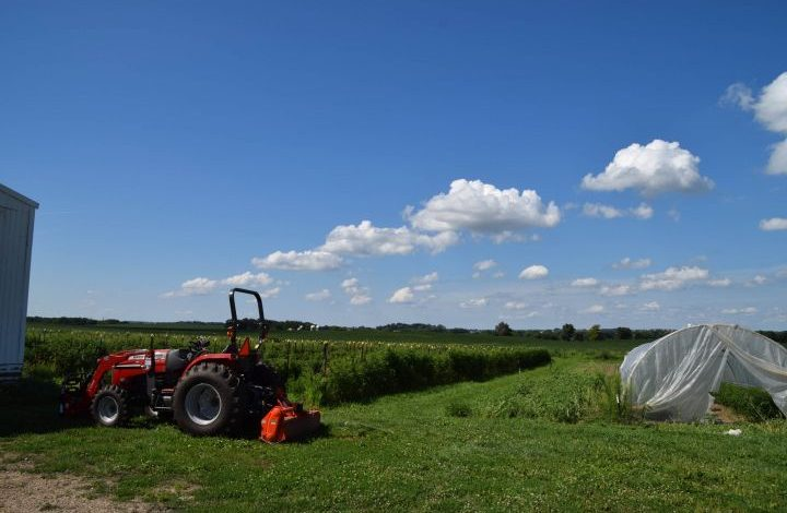 Red tractor next to a hoop house in front of a field
