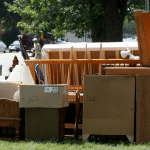 Furniture and boxes are piled on the grass ready for a moving van
