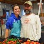 Cate and Mat Eddy, the farmers at Ridgeland Harvest, stand in front of a crate of brightly colored peppers in their pack shed