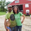 Family portrait showing Adam, Jillian and Ayla Varney in the barnyard of Small Family CSA Farm in La Farge, Wisconsin.