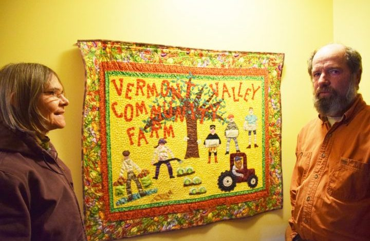 Barb and David with a handmade quilt hung on a wall, depicting their family working together on their farm