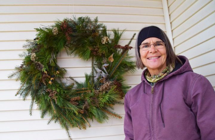 Barb next to an evergreen holiday wreath