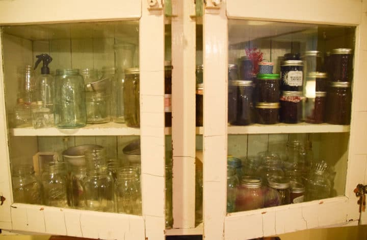 Cupboard with canning jars - some full, some empty