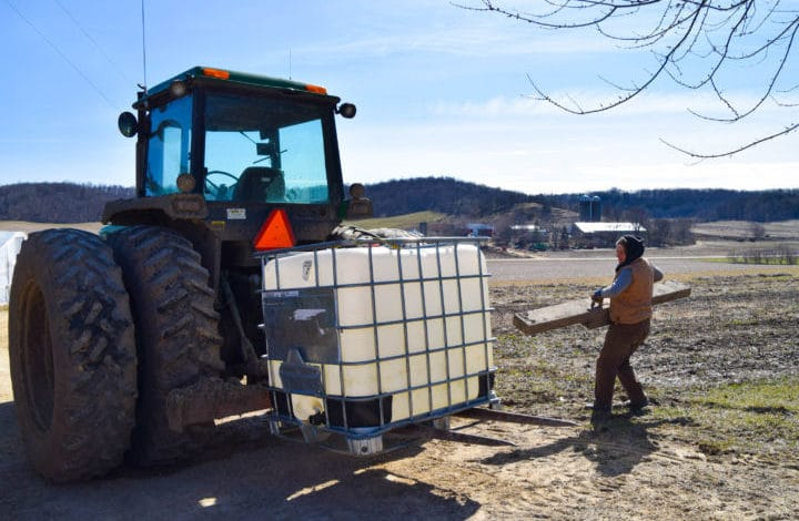 Farmer moving long piece of wood to back of tractor carrying tote