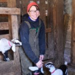 Farmer Diana Murphy with goat kids in barn stall