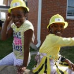 Photo of kids at play in hardhats at tVera Court Community Center. From veracourt.org